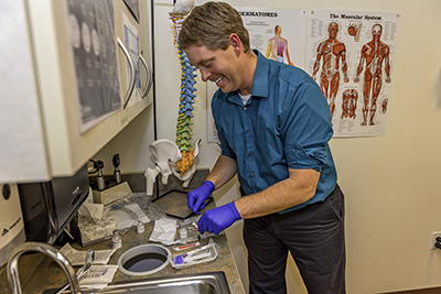 """Montana native Dr. Craig Sweeney prepares for his next patient at the Great Falls Clinic. """"Before you even have anything done, he makes you feel better because he is so positive,"""" remarks one of his thankful clients."""