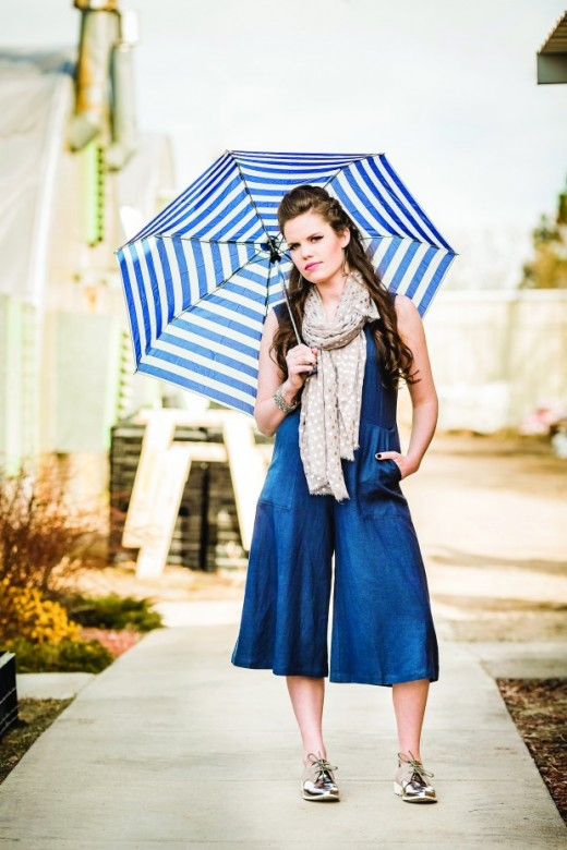 AMBER: Lush blue jumper, Seychelles mirrored Oxfords, GoodWorks silver leather and silver chain bracelet,  Printed Village polka dot scarf and silver dangle earrings with blue accent. All from Sole Sisters. (pg. 83). Models own umbrella.